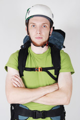 mountain tourist in helmet and with big backpack standing with c