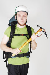 mountain tourist in helmet and with big backpack standing and ho