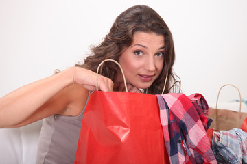 Young woman at home examining shopping bags