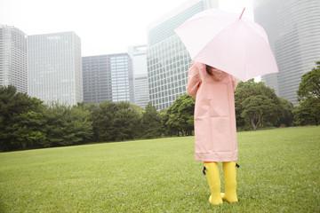 傘をさして公園に立つ女性の後姿