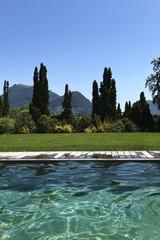 piscina, prato alberi e montagne o monti