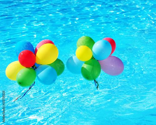 Leinwandbild Motiv Balloons floating in swimming pool.
