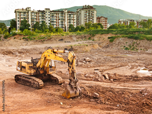 bulldozer machine excavating earth near city
