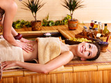 Fototapety Woman getting massage in bamboo spa.