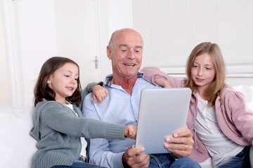 Grandfather with kids using electronic tablet