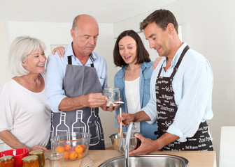 Family preparing fruit jam in home kitchen