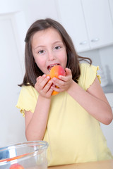 Portrait of little girl eating apricots