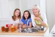 Senior woman making apricot jam with grandkids