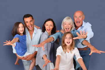 Portrait of happy family standing ion grey background