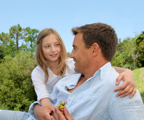 Father and daughter sitting in park