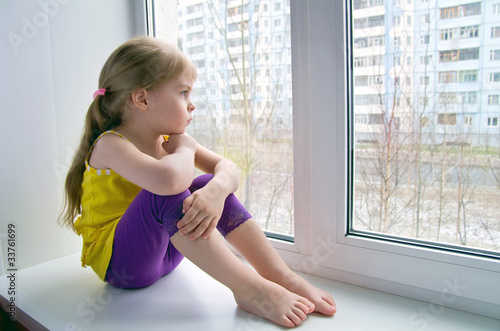 Sad child at the window.