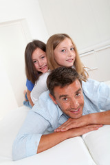 Man lying down on sofa with girls on his back