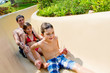 Father and Children Sliding Down Water Slide