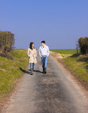 Couple of young people walking in the campaign in spring poster