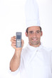 Chef holding up a telephone