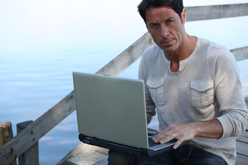Man using a laptop computer by the water