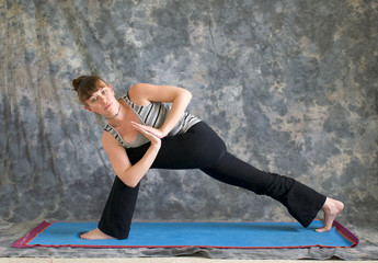 woman doing Yoga posture Parivrtta Parsvakonasana or Revolved Ex