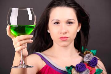 Красивая девушка улыбается и держит бокал с напитком