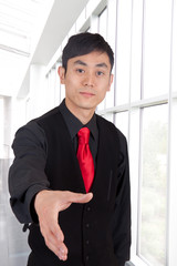 A Japanese businessman dressed in black with hand outstretched.