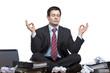 Gestresster, frustrierter Geschäftsmann meditiert im Büro