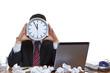 Mann im Büro unter extremen Zeitruck hält Uhr vor Gesicht