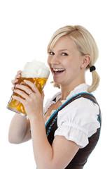 Hübsche junge blonde Frau im Dirndl trinkt aus Oktoberfest Mass