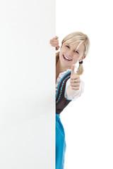 hübsches blondes Mädchen im Dirndl zeigt Daumen u. hält Werbesch