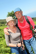 Portrait of happy senior couple hiking in natural landscape
