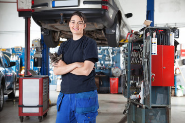 Smiling young female mechanic in garage