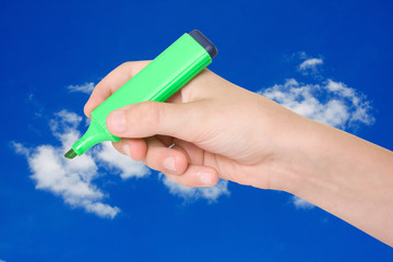 hand with a marker over a blue sky background.