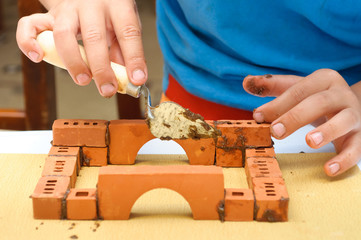 Children build a small house made ​​of bricks