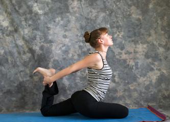 young woman doing Yoga posture Kapotasana or Pigeon Pose variati