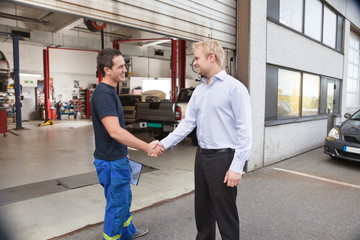 Mechanic shaking hands with client