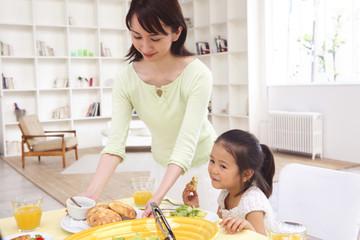 食卓に料理を並べる母親