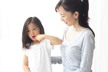 歯を磨いている女の子とその母親