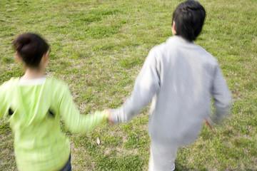 手をつないで走るカップル