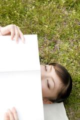 芝生に寝転び本を読む女性