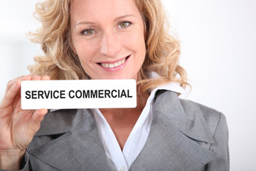 Woman holding Service Commercial sign