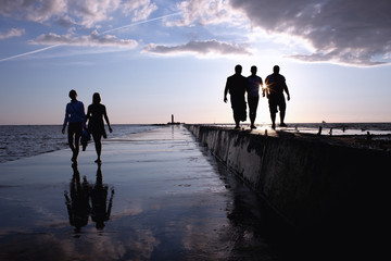Silhouettes of three men and a pair of women against the sea