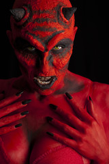 Sexy red devil woman, black background.