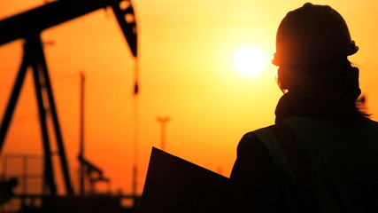 Engineer Oil Drilling in Silhouette at Sunset