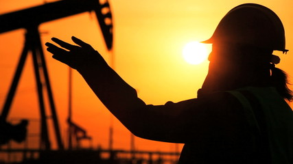 Engineer in Silhouette at Oil Production Site