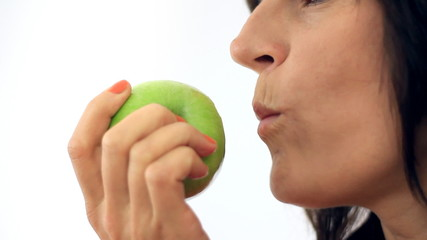 Female mouth eating apple, close-up, isolated