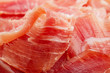 Spanish Serrano Ham Jamon sliced closeup background