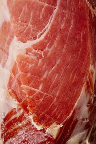 Spanish Serrano Ham Jamon sliced closeup background