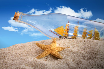 Ship in a bottle in a pile of sand