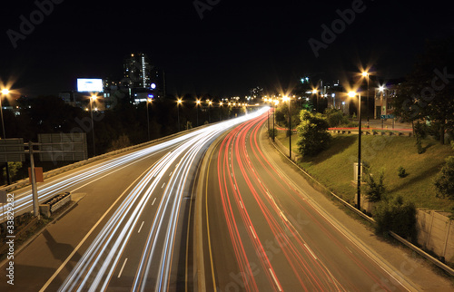 Foto op Aluminium Nacht snelweg Moving vehicles create light trails along a highway at night