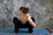young woman doing Yoga posture bound Malasana or garland squat p
