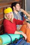 Tramping young couple backpack relax by cottage poster