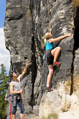 Rock climbing male instructor blond woman sunny